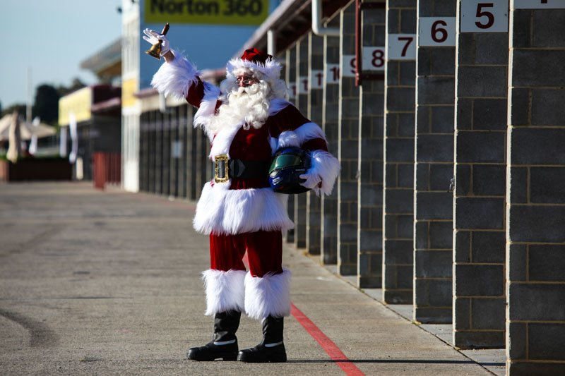 Real Santa standing with bell in air outside track
